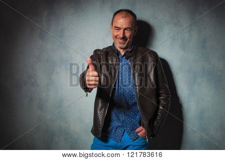 portrait of mature man in leather jacket showing thumbs up with hand in pocket while looking at the camera in gray studio background