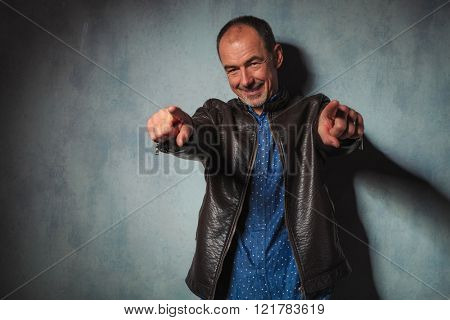 portrait of mature man standing and pointing both hands to the camera while while posing in gray studio background