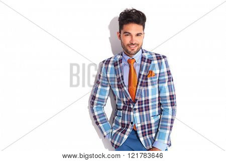 portrait of smart casual man in plaid jacket looking at the camera with hand in pocket in white studio background