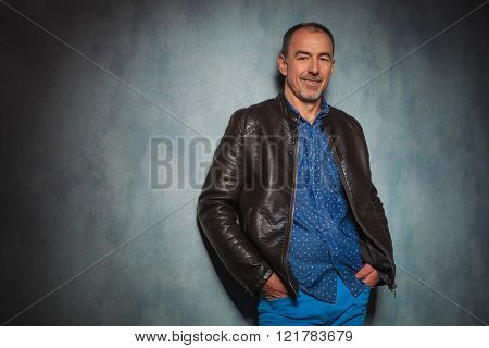 portrait of handsome mature man in leather jacket standing in gray studio background with both hands in pockets while looking at the camera