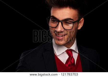 close portrait of attractive young man in suit, wearing tie and glasses, looking away from the camera in dark studio background
