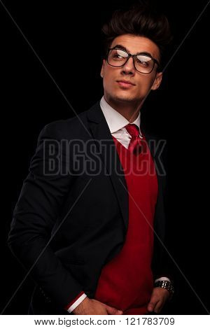 classy model wearing black suit with glasses, posing with hands in pockets while looking away from the camera in dark studio background
