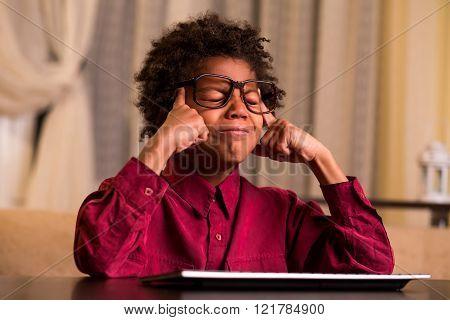 Upset black boy at keyboard.
