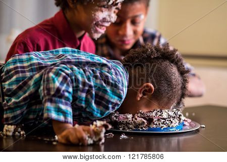 Afro boy's face smashing cake.
