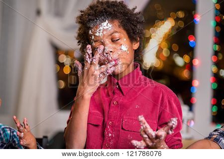Kid licks cake-smeared fingers.