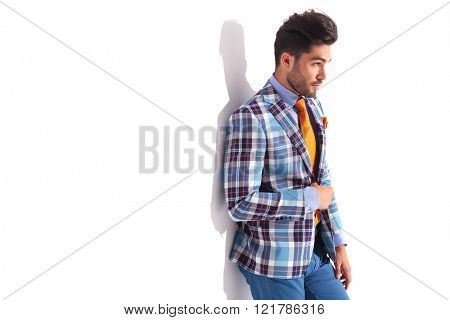 close portrait of casual man standing in studio background while fixing his plaid jacket and looking at away from the camera
