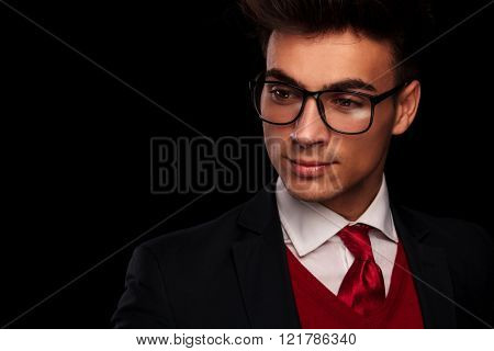 close portrait of businessman in black suit wearing glasses, looking away from the camera in dark studio background