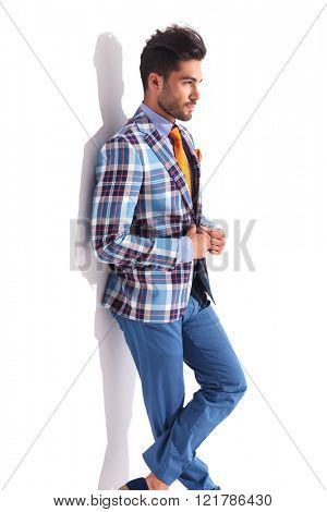smart casual man standing with legs crossed in studio background while fixing his plaid jacket and looking away from the camera