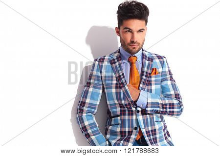 close portrait of man with hand in plaid jacket posing while looking away from the camera in white studio background