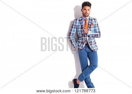 smart casual man with hand in pocket posing with hand in jacket and legs crossed while looking away from the camera in white studio background