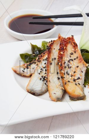 Eel Sashimi With Soy Sauce On A White Plate Over Wooden Background