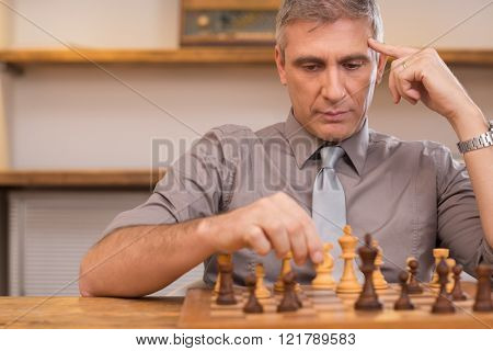 Mature man thinking while playing chess. Portrait of concentrated businessman playing chess. Senior chess player deeply concentrated on the chessboard at office. Business strategy concept.