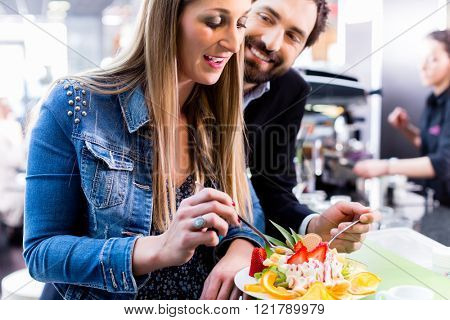 Woman eating fruit sundae in ice cream cafe