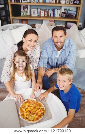 High angle portrait of family with pizza on table at home
