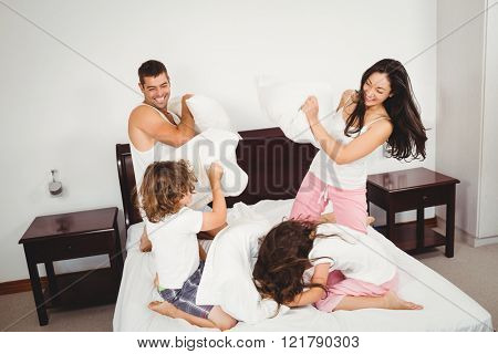 Cheerful family pillow fighting on bed at home