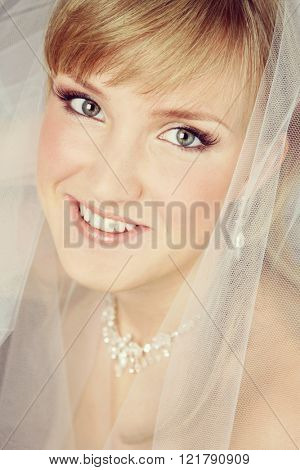 Vintage style close-up portrait of young beautiful happy smiling bride with bridal veil