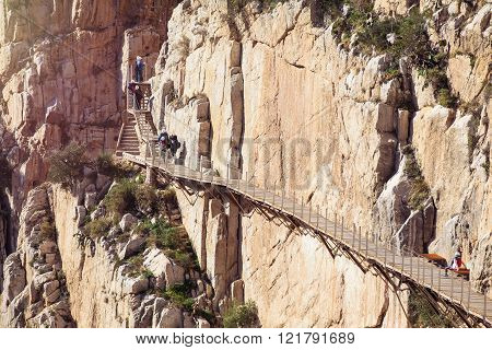 EL CHORRO, SPAIN - DECEMBER 19, 2015: People crossing a gangway in the Caminito del Rey Route, in El Chorro, Malaga, Spain, in December 19, 2015. Caminito del Rey is a very famous hiking route in Malaga province.