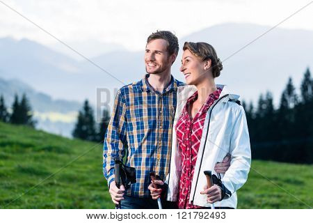 Couple enjoying view hiking in the alpine mountains