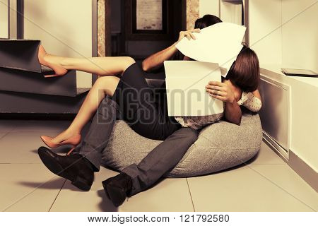Young business couple flirting in office