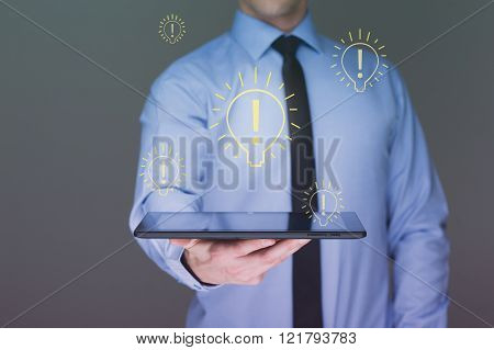 light bulb money on tablet businessman.