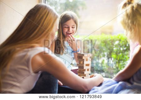 Happy Mother With Two Children Playing The Wooden Blocks Tower
