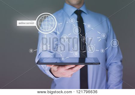 Businessman holding a tablet pc with online service text on virtual screen. Internet concept.