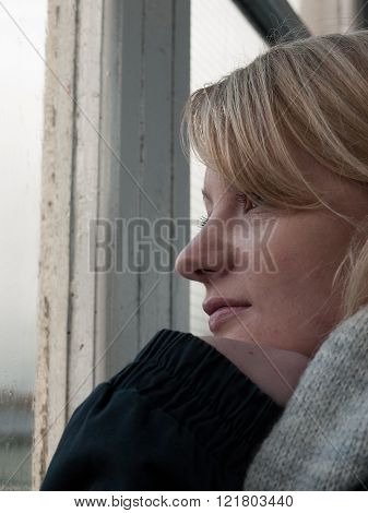 A young blonde woman looking out of window. She appears to be contemplating something.