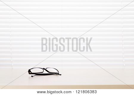 Office workplace with glasses on wood desk table in front of window with blinds