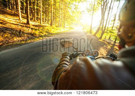 Motorcyclist riding motorbike in sunny morning