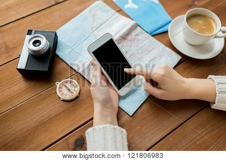 vacation, tourism, travel, technology and people concept - close up of traveler hands with blank smartphone screen and map