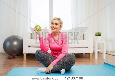 healthy eating, organic food, diet and people concept - happy woman eating green apple at home