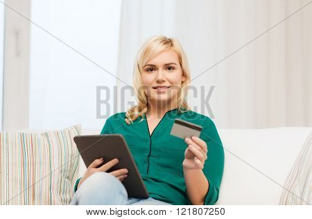 people, internet bank, online shopping, technology and e-money concept - happy young woman sitting on sofa with tablet pc computer and credit card at home