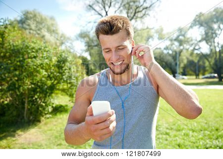 fitness, sport, technology and lifestyle concept - happy young man with smartphone and earphones listening to music at summer park