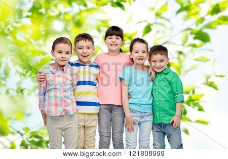 childhood, summer, fashion, friendship and people concept - group of happy smiling little children hugging over green natural background