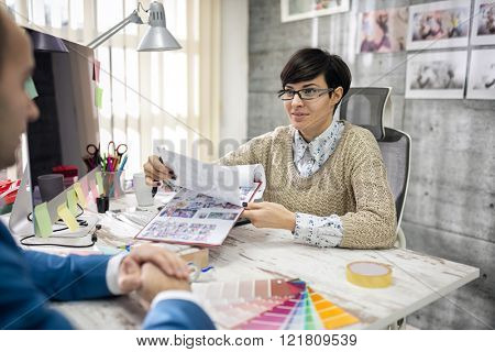 designer showing palette color to client in her studio