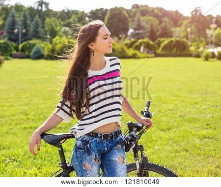 Young woman enjoy weather with her bike in city park at summer day