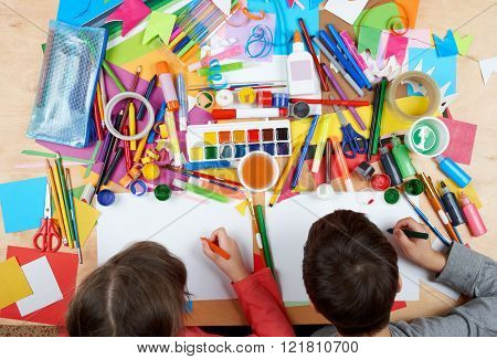 Child drawing top view. Artwork workplace with creative accessories. Flat lay art tools for painting.