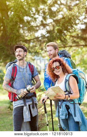 Group of hikers in forest with backpack, thermos, map and hiking sticks in green forest