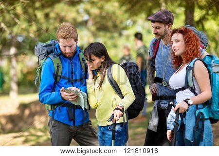 Chap and lassie from hiking group with backpack study map in nature