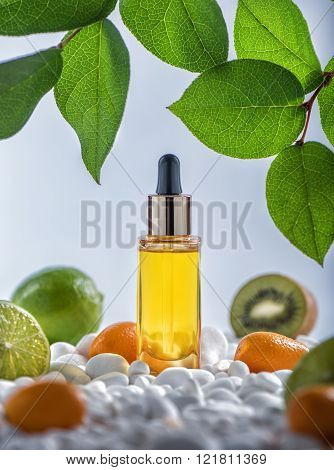 The bottle of fruit cosmetic  moisturizing oil with white stones and fruits