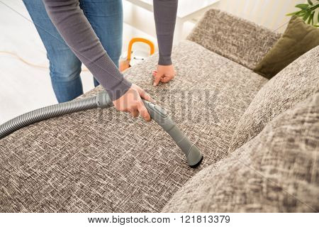 Vacuuming sofa with vacuum cleaner in living room