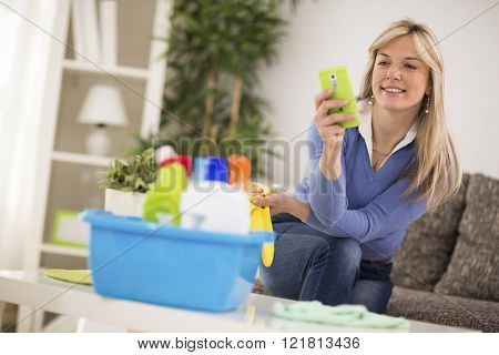 Attractive blond woman look at mobile phone during break from cleaning house