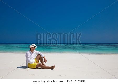 Summer beach. Relax. Successful handsome man in hat resting on exotic seashore with blue water and white sand. Vacation Travel. Bliss freedom concept.