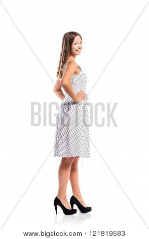 Girl in black-and-white dotted dress, heels, studio shot