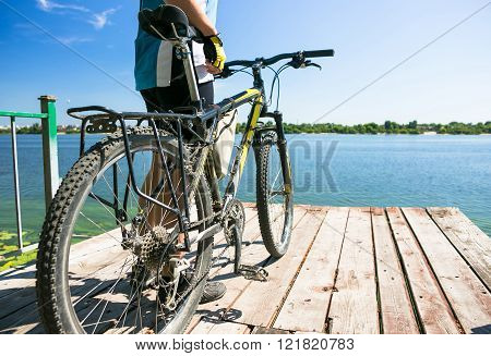 Bicyclist relax in a pear near river. Sunny summer hot day