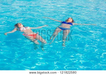 Two Beautiful Women Lying On Swimming Pool Water Surface
