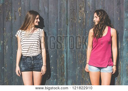 Portrait Of Two Beautiful Girls With Wooden Background