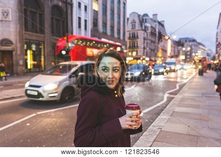 Woman In London Standing By A Busy Road At Night