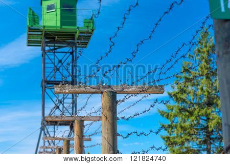 green tower and barbed wire on the border