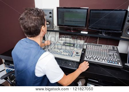 Man Mixing Audio In Recording Studio